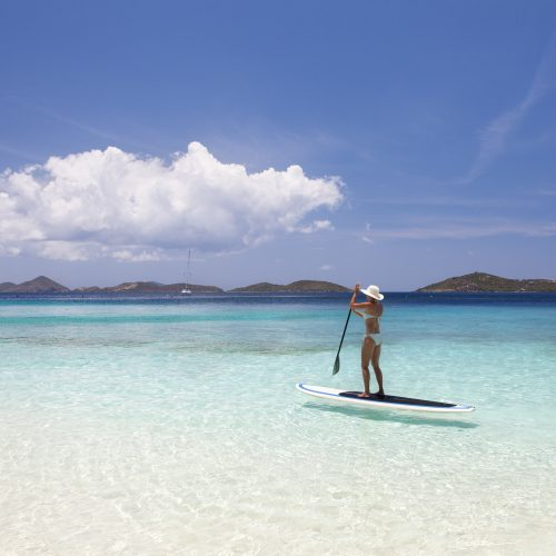 woman in bikini enjoying stand up paddle boarding in the crystal clear water of the Caribbean